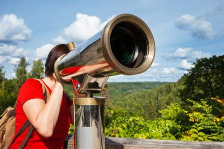 Young woman looking through tourist telescope, exploring landscape. Selective focus on telescope. photo