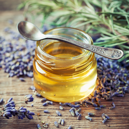 blossom honey: Jar of honey, spoon and dry lavender flowers for tea. Selective focus.