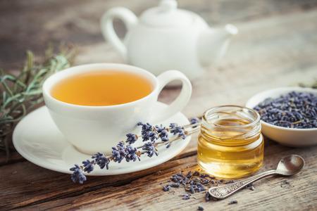 Gezonde theekop, kruik honing, droge lavendelbloemen en theepot op achtergrond. Selectieve aandacht. Retro stijl. Stockfoto