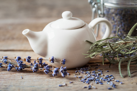 Teapot of healthy herbal tea, dry lavender flowers and jar with dry lavender. Selective focus. Retro styled.