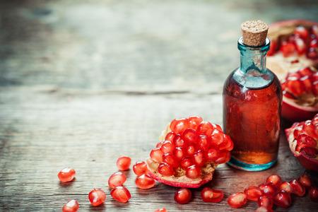 나무 테이블에 씨앗 석류 팅크 또는 주스와 빨간색 잘 익은 석류 열매. 선택적 중점을두고 있습니다.