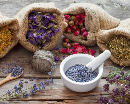 medicina natural: Hierbas curativas en bolsas de arpillera y el mortero con lavanda seca, hierbas medicinales. Foto de archivo