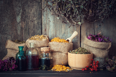 Healing herbs in hessian bags, mortar and bottles of tincture or oil, herbal medicine.