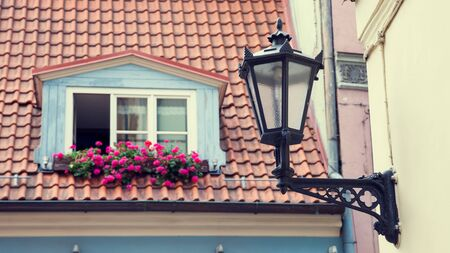 old buildings: Vintage street lamp on wall and window in garret roof on background. Selective focus. Stock Photo