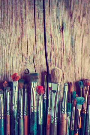 painter palette: Row of artist paintbrushes closeup on old wooden rustic background, retro styled. Stock Photo