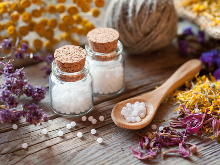 globules: Bottles of homeopathy globules, wooden spoon and dry healthy herbs. Selective focus. Stock Photo