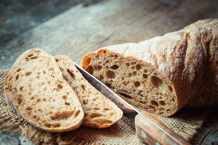cuchillo: rebanada de pan fresco y un cuchillo de cortar en la mesa rústica