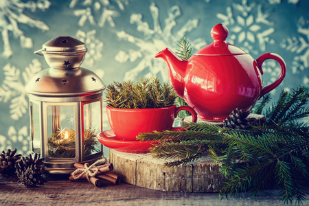 arrangements: Christmas decoration: lantern with candle, tea kettle and cup with spruce twigs. Stock Photo