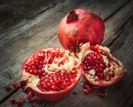 Ripe pomegranate slice and whole red garnet fruit on table. Selective focus. Retro styled.