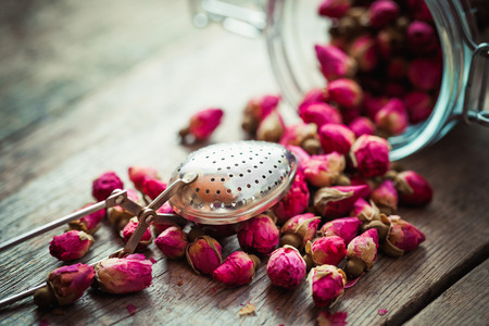 infuser: Rose buds, tea strainer and glass jar on rustic wooden table. Retro styled. Selective focus.
