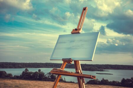 artists: Blank artist canvas rests on a easel on lake landscape, retro styled photo.