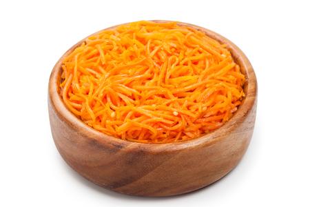 korean salad: Grated carrots. Korean salad in wooden bowl on white. Stock Photo