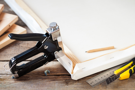 Artist canvas, canvas brancard en nieten pistool op tafel