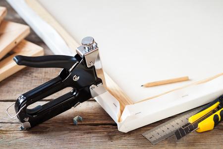 estiramientos: lienzo del artista, camilla de lona y la pistola de grapas en la mesa Foto de archivo