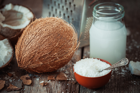 grounded: Coconut milk, grounded coconut flakes, fresh coco nut and grater on background. Stock Photo