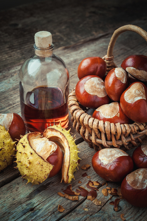 horse chestnut seed: Brown chestnuts in basket and bottle of healthy tincture on old wooden table. Retro styled.