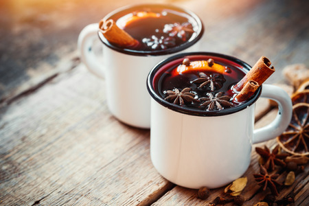 vin chaud: Mulled wine in white rustic mugs with spices and citrus Banque d'images