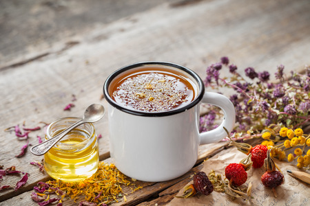 rustical: Cup of healthy daisy tea, honey and healing herbs on table. Herbal medicine. Stock Photo