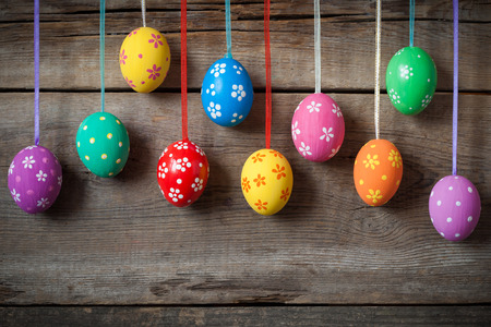 rustic: Hanging colorful eggs on rustic wooden background Stock Photo