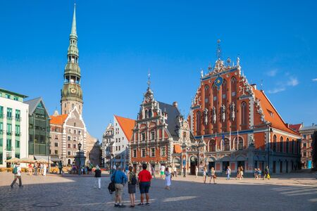 old town house: Riga, Latvia - 24-August-2015: Town Hall Square - house of the Blackheads, sculpture of Saint Roland and Saint Peters Church in old city Riga, Latvia