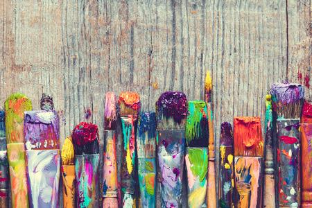 fila: Fila de cepillos de pintura del artista primer en el fondo de madera vieja.