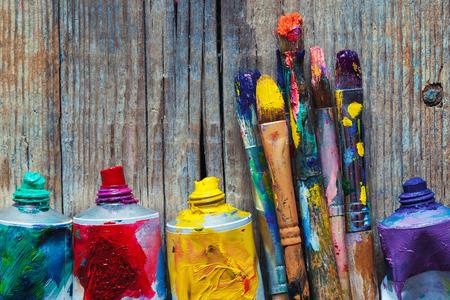 オイル ペイントと木製の背景でペイント ブラシのクローズ アップをアーティストのチューブ。レトロな。