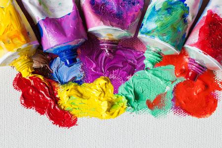 Tubes of oil paint and artist paintbrushes closeup on artistic canvas Foto de archivo