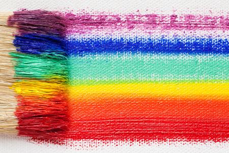 brocha de pintura: Pincel de cerdas pinceladas primer y el arco iris multicolor sobre lienzo del artista