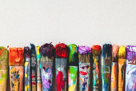 brocha de pintura: Fila de pinceles artista portarretrato sobre lienzo artístico.