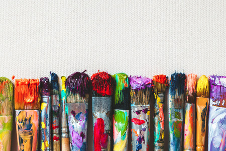 fabric painting: Row of artist paintbrushes closeup on artistic canvas.