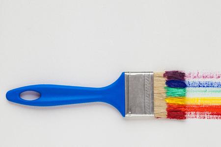 Paintbrush avec poignée et multicolore arc bleu coups de pinceau sur une toile blanche de l'artiste