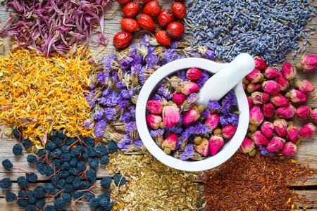 Mortar of healing herbs, herbal tea assortment and berries on table. Top view. Herbal medicine.