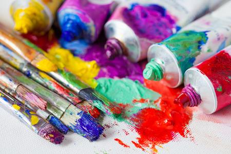 Buizen van veelkleurige olieverf en kunstenaar penselen op canvas close.