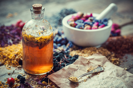 herbal cosmetics: Tincture bottle, mortar of healing herbs and paper of recipes on table. Herbal medicine. Stock Photo
