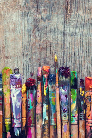 Row of artist paint brushes closeup on old rustic wooden background. Archivio Fotografico