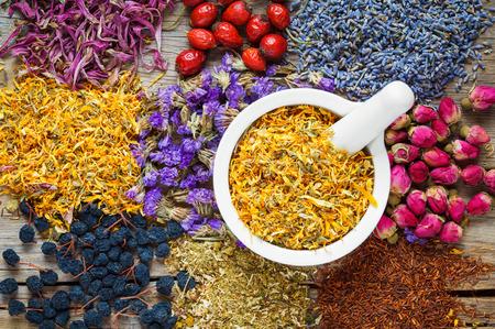 Mortar of dry marigold flowers, healthy herbs, herbal tea assortment and berries on old wooden table. Herbal medicine.