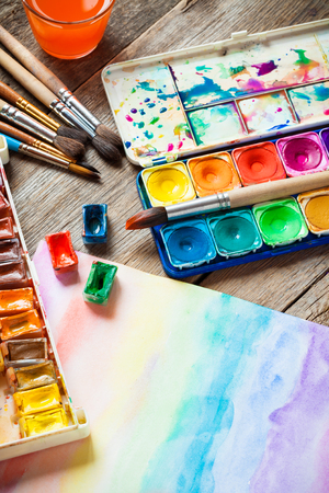 Watercolor paints, brushes for painting and paper sheet of painting on old wooden background. Top view. Stock Photo