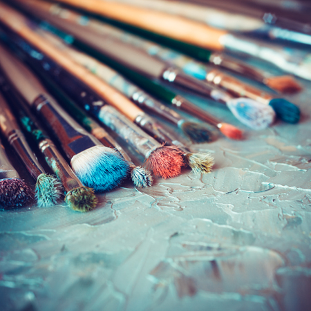 at paint: Artistic paintbrushes on artist canvas covered with oil paints