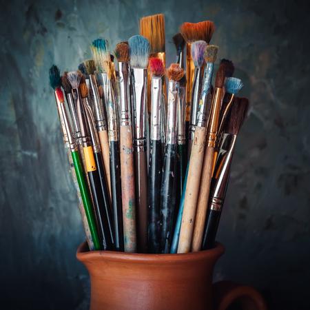 brocha de pintura: Pinceles en una jarra de barro cocido de alfarero en el fondo jadeo oscuro.