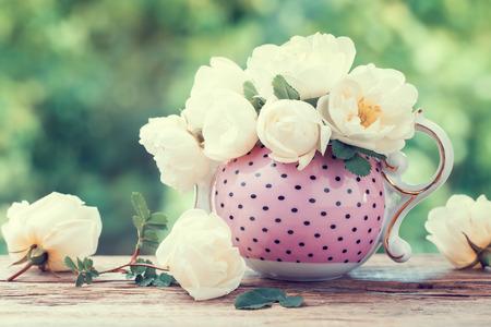 garden flowers: Bouquet of roses in tea kettle. Wedding or birthday still life. Retro styled.