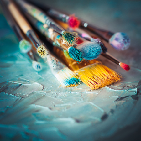 priming brush: Paintbrushes on artist canvas covered with oil paints. Retro styled. Stock Photo