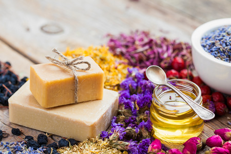 homemade: Bars of homemade soaps, honey or oil, heaps of healing herbs and mortar of lavender. Selective focus.