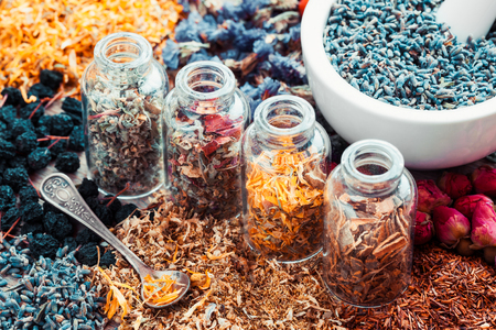 Bottles of healing herbs and mortar with lavender flowers, herbal medicine. Retro styled. 版權商用圖片