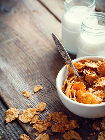 breakfast bowl: Breakfast cereal wheat flakes in bowl and milk bottles on wooden table