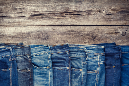 jeanswear: Fashion different jeans on wooden background. Retro toned.