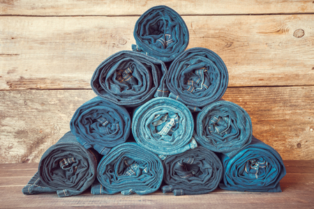 Rolled jeans stack on wooden background, retro toned. Stock Photo