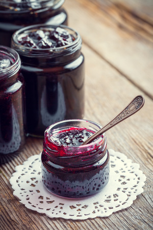 red currant: Jars of jam on wooden kitchen table. Retro toned.