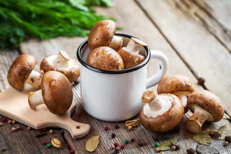 enameled: Mushrooms in enameled mug, dill and spices on wooden table. Stock Photo