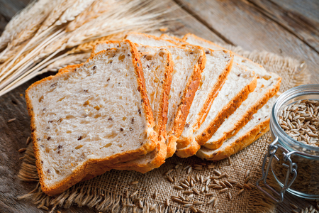 wheat toast: Wheat toast bread, spikes and wheat grains on kitchen table. Stock Photo