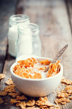 breakfast bowl: Breakfast cereal wheat flakes in ceramic bowl and milk bottles on wooden table